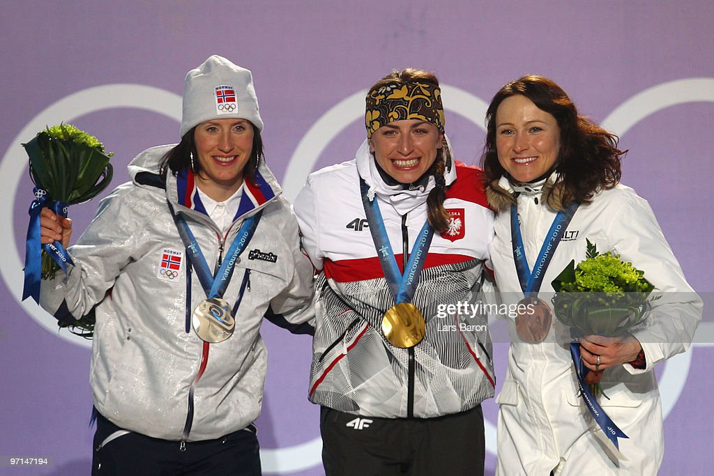 <a gi-track='captionPersonalityLinkClicked' href=/galleries/search?phrase=Marit+Bjoergen&family=editorial&specificpeople=216406 ng-click='$event.stopPropagation()'>Marit Bjoergen</a> of Norway celebrates her Silver medal, Justyna Kowalczyk of Poland Gold, and <a gi-track='captionPersonalityLinkClicked' href=/galleries/search?phrase=Aino-Kaisa+Saarinen&family=editorial&specificpeople=769322 ng-click='$event.stopPropagation()'>Aino-Kaisa Saarinen</a> of Finland Bronze during the medal ceremony for the Ladies Cross Country 30 km Mass Start Classic during the medal ceremony on day 16 of the Vancouver 2010 Winter Olympics at Whistler Medals Plaza on February 27, 2010 in Whistler, Canada.