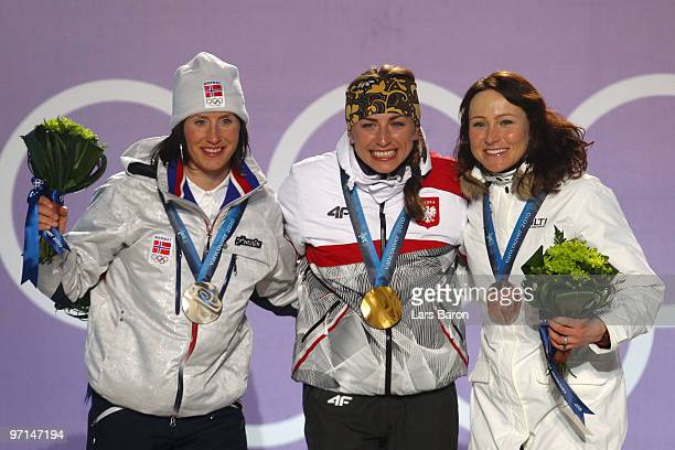 Marit Bjoergen of Norway celebrates her Silver medal Justyna Kowalczyk of Poland Gold and AinoKaisa Saarinen of Finland Bronze during the medal...