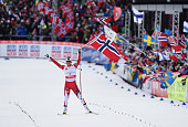 Marit Bjoergen of Norway celebrates on the way to winning the gold medal in the Women's 4 x 5km CrossCountry Relay during the FIS Nordic World Ski...