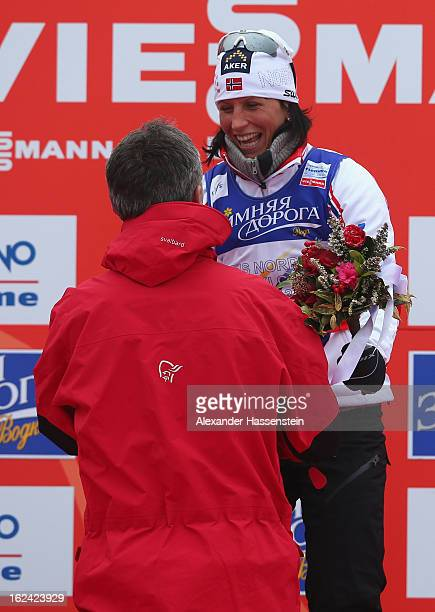 Marit Bjoergen of Norway is congratulated on the podium by Norwegian Prime Minister Jens Stoltenberg after the Women's Skiathlon 75km at the FIS...