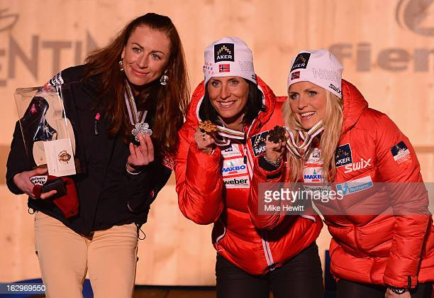 Marit Bjoergen of Norway poses with her Gold medal on the podium with Silver medalist Justyna Kowalczyk of Poland and Bronze medalist Therese Johaug...