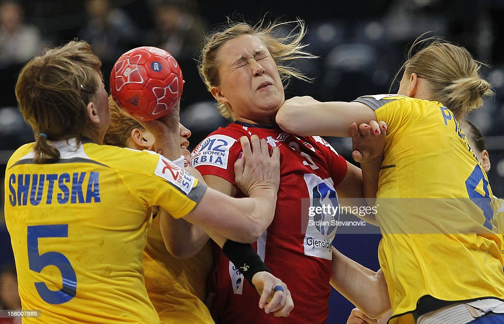 Marit Malm Frafjord (C) of Norway is challenged by Iryna Shutska (L) and Anastasiia Pidpalova (R) of Ukraine during the Women's European Handball Championship 2012 Group A match between Norway and Ukraine at Arena Hall on December 08, 2012 in Belgrade, Serbia.