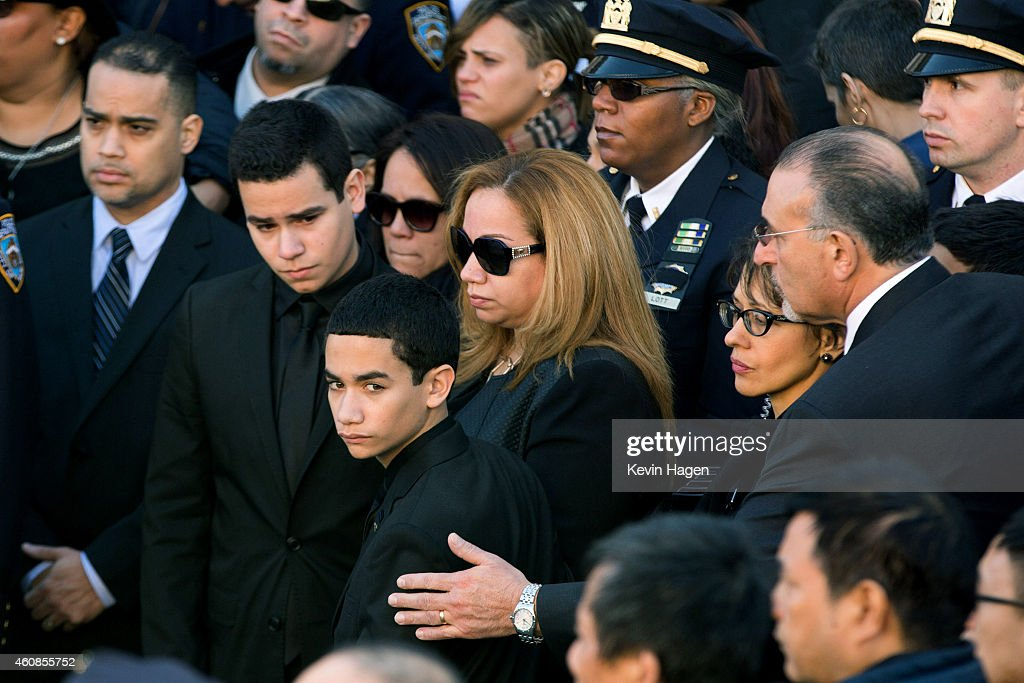 Maritza Ramos wife of the victim is joined by her sons Justin left and Jaden during the funeral of slain New York Police Department officer Rafael...