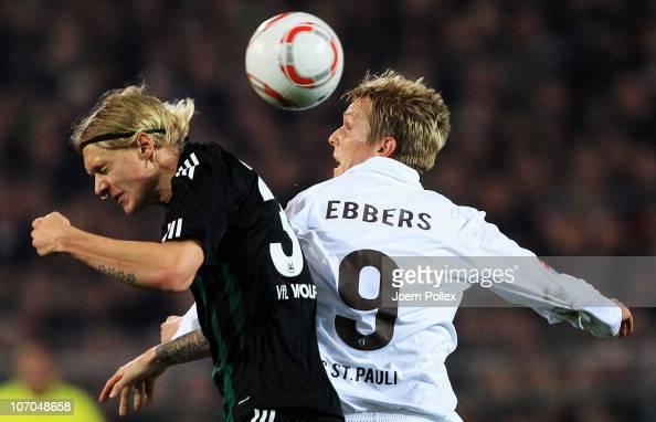 Marius Ebbers of Hamburg and Simon Kjaer of Wolfsburg jump for a header during the Bundesliga match between FC St Pauli and VfL Wolfsburg at...