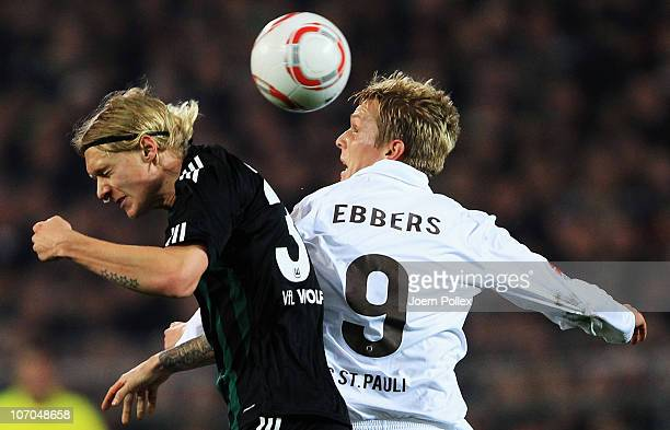 Marius Ebbers of Hamburg and Simon Kjaer of Wolfsburg jump for a header during the Bundesliga match between FC St Pauli and VfL Wolfsburg at...