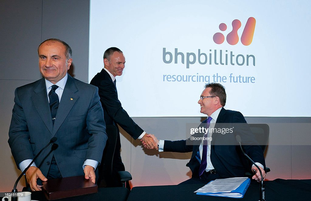 Marius Kloppers, chief executive officer of BHP Billiton Ltd., center, shakes the hand of Andrew Mackenzie, chief executive officer for non-ferrous, right, as Jacques 'Jac' Nasser, chairman, looks on at a news conference in Sydney, Australia, on Wednesday, Feb. 20, 2013. BHP Billiton, the world's biggest mining company, named its copper unit head Andrew Mackenzie as chief executive officer to succeed Marius Kloppers before reporting a 58 percent decline in first-half profit. Photographer: Ian Waldie/Bloomberg via Getty Images Marius Kloppers; Jac Nasser; Andrew Mackenzie