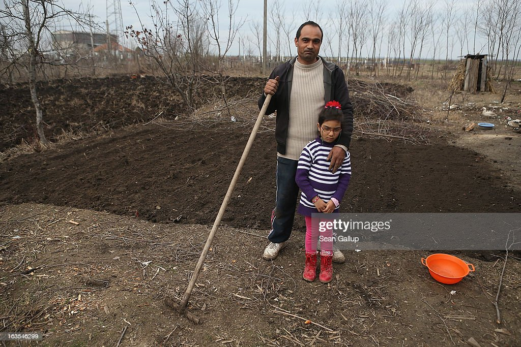 Marius Tanase, an ethnic Roma, and his daughter Denisa, 6, take a break while planting onions in their vegetable garden outside their home on March 11, 2013 in Dilga, Romania. Marius worked construction jobs in Spain and Great Britain and says he would like to move permanently to Great Britain, not because of the money but because he thinks his five children will have a better chance at a full education and brighter future than in Romania. Dilga is a settlement of 2,500 people with dirt roads and no running water, and unemployment is at 70%. Most of the working-age men and women have at some point worked abroad, mostly in Italy or Great Britain, as many say they are unable to find adequate work in Romania. Romania's Roma belong to a myriad of different tribes defined by their craft, and Dilga's belong to a group called the Rudari, who until the 1930s specialised in woodcrafts. During the communist years most worked in nearby state-run factories and agricultural cooperatives, though the majority of these went bankrupt after 1989 and the local Roma lost their jobs. Since then they have struggled to make ends meet and find a better future for their children, though projects initiated by the European Union and NGOs are helping some to launch small-scale enterprises and improve their children's education.