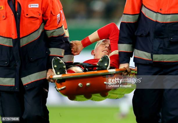 Marius Wolf of Frankfurt is carried injured off the pitch during the DFB Cup semi final match between Borussia Moenchengladbach and Eintracht...