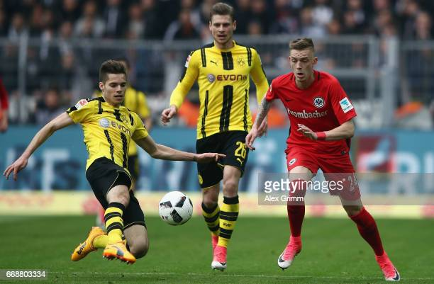 Marius Wolf of Frankfurt is challenged by Julian Weigl of Dortmund during the Bundesliga match between Borussia Dortmund and Eintracht Frankfurt at...