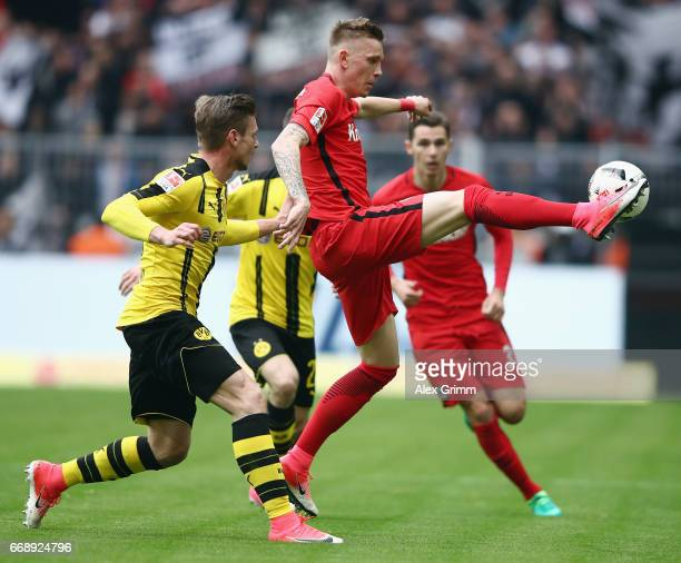 Marius Wolf of Frankfurt is challenged by Lukas Piszczek of Dortmund during the Bundesliga match between Borussia Dortmund and Eintracht Frankfurt at...