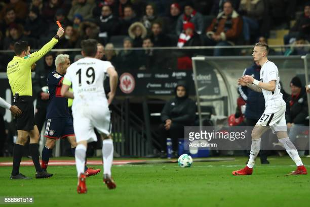 Marius Wolf of Frankfurt is shown a red card by referee Harm Osmers which he later corrected into a yellow card during the Bundesliga match between...
