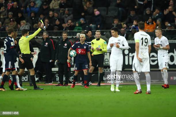 Marius Wolf of Frankfurt is shown a yellow card by referee Harm Osmers for a foul he earlier judged to be a red card during the Bundesliga match...