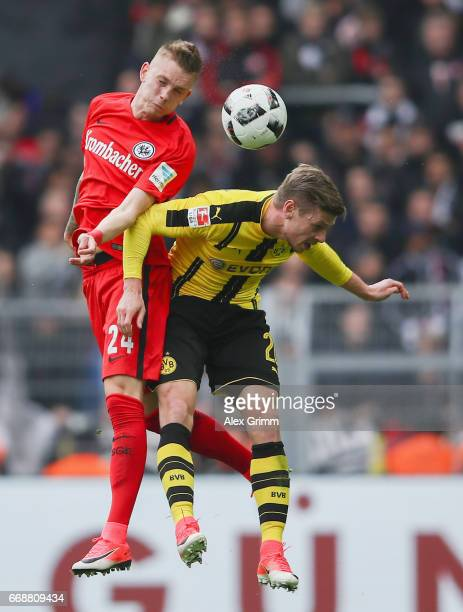 Marius Wolf of Frankfurt jumps for a header with Lukas Piszczek of Dortmund during the Bundesliga match between Borussia Dortmund and Eintracht...
