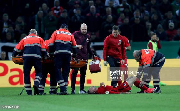 Marius Wolf of Frankfurt lies injured on the pitch during the DFB Cup semi final match between Borussia Moenchengladbach and Eintracht Frankfurt at...