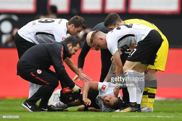 Marius Wolf of Frankfurt lies on the pitch injured as his team mates and medics check on him during the Bundesliga match between Eintracht Frankfurt...