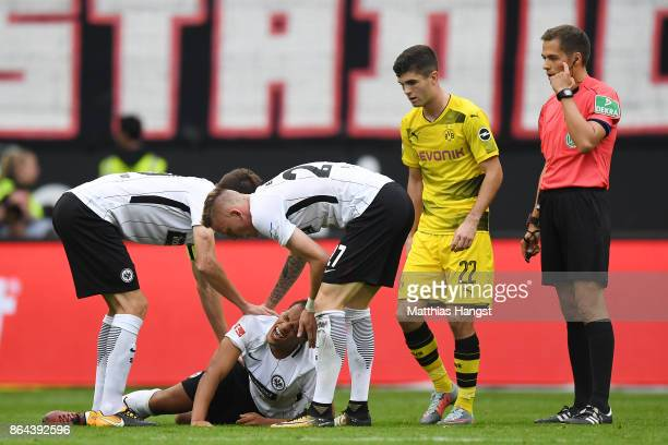 Marius Wolf of Frankfurt lies on the pitch injured as his team mates check on him during the Bundesliga match between Eintracht Frankfurt and...