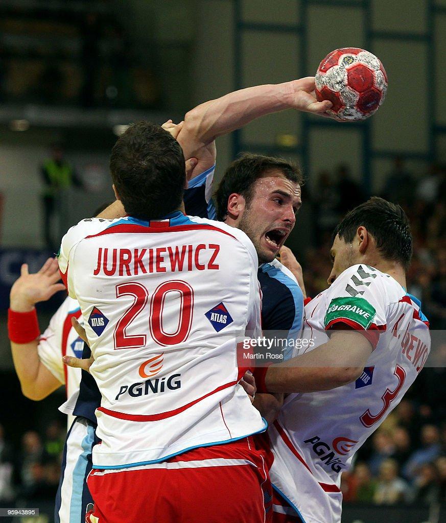 Mariusz Jurkiewicz and Krysztof Lijewski of Poland challenge Uros Zorman of Slovenia during the Men's Handball European Championship Group C match...