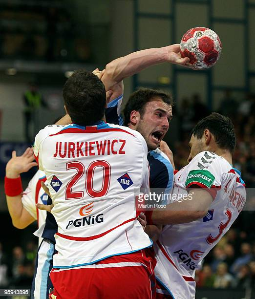 Mariusz Jurkiewicz and Krysztof Lijewski of Poland challenge Uros Zorman of Slovenia during the Men's Handball European Championship Group C match...