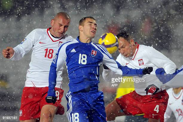 Mariusz Lewandowski and Arkadiusz Glowacki of Poland vie with Erik Jendrisek of Slovakia during the 2010 World Cup Group 3 qualifier match between...