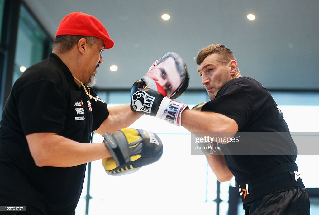 Mariusz Wach of Poland warms up with his coach Juan DeLeon during a public training session at Mercedes Benz car dealer on November 7 2012 in Hamburg...