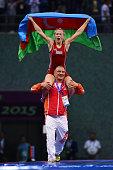 Mariya Stadnyk of Azerbaijan is carried aloft of the shoulders of her coach Simeon Shterev after defeating Elitsa Yankova of Bulgaria in the Women's...