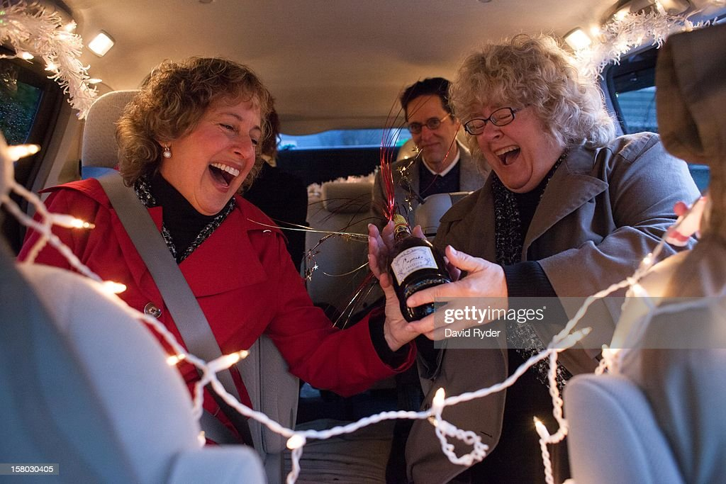 Marji Lynn, left, and Sue Hopkins share a laugh after being surprised with champagne and a decorated minivan before they leave for City Hall to get married on December 9, 2012 in Seattle, Washington. Today is the first day that same-sex couples can legally wed in Washington state.