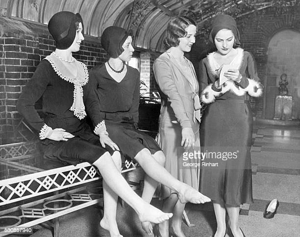 Marjorie Ekdahl Miss America is shown taking notes on the feet being displayed by Eunice McGinnis Alice Roddish and Mrs David Wallace for a contest...