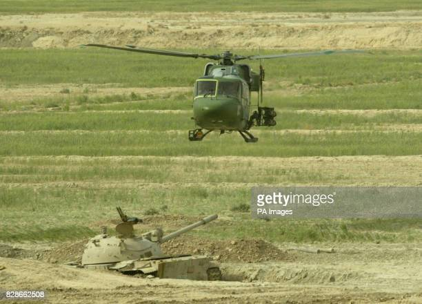 A Mark 7 Lynx helicopter from 3 Reg Army Air Corps 16 Air Assault Brigade on a combat patrol carrying TOW missiles flies over a destroyed Iraqi T55...