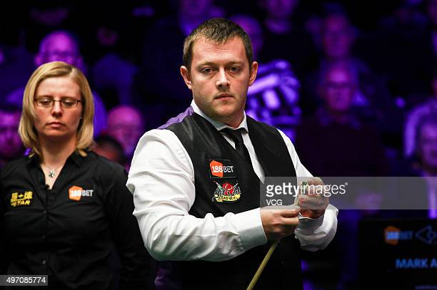 Mark Allen of England chalks his cue in the first round match against Barry S Hawkins of England on day four of Champion of Champions 2015 at Ricoh...