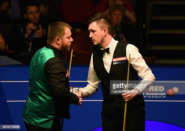 Mark Allen of Northern Ireland congratulates Kyren Wilson of England during their second round match on day ten of the World Snooker Championship at...
