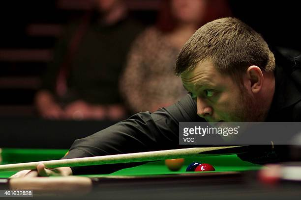 Mark Allen of Northern Ireland plays a shot against Joe Perry of England during day six of the 2015 Dafabet Masters at Alexandra Palace on January 16...