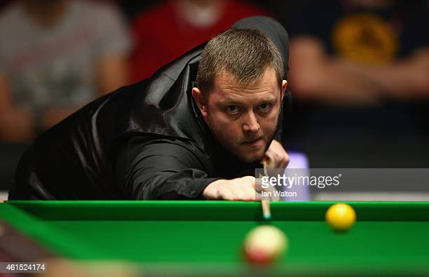 Mark Allen of Northern Ireland plays a shot during his first round match against John Higgins of Scotland on Day Four of the 2015 Dafabet Masters at...