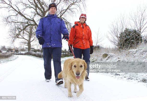 Mark and Catherine Kaye walk their dog Barney down a snow covered lane near Catterick North Yorkshire