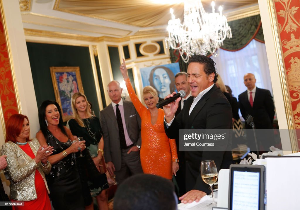 Mark Antonio Rota (R) sings for guest during the exhibition of artwork featuring Giovanni Perrone and hosted by Ivana Trump and Mark Antonio Rota on April 30, 2013 in New York City.