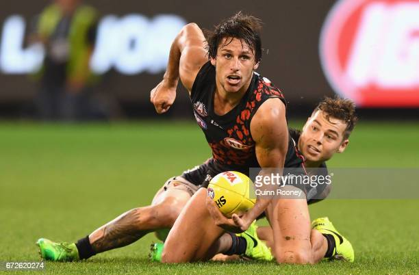Mark Baguley of the Bombers handballs whilst being tackled by Jamie Elliott of the Magpies during the round five AFL match between the Essendon...