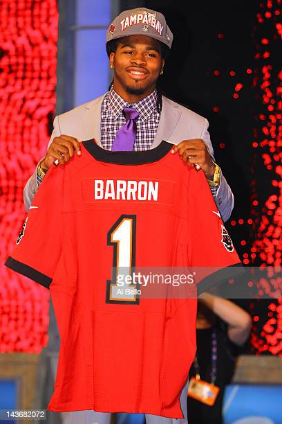 Mark Barron of Alabama holds up a jersey as he stands on stage after he was selected overall by the Tampa Bay Buccaneers in the first round of during...