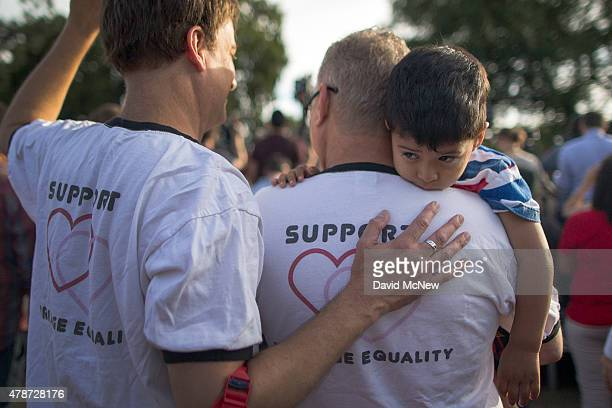 Mark Beckfold and Steve Ledoux who are married hold their foster son at a celebration of the Supreme Court ruling on samesex marriage on June 26 2015...