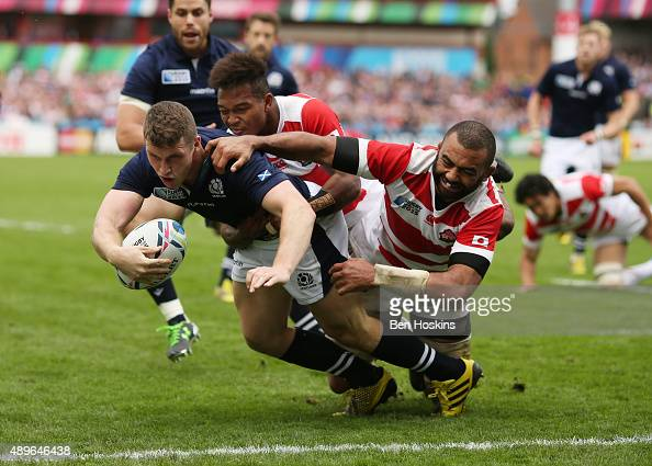Mark Bennett of Scotland goes over to score his teams 4th try despite a tackle by Michael Leitch of Japan during the 2015 Rugby World Cup Pool B...