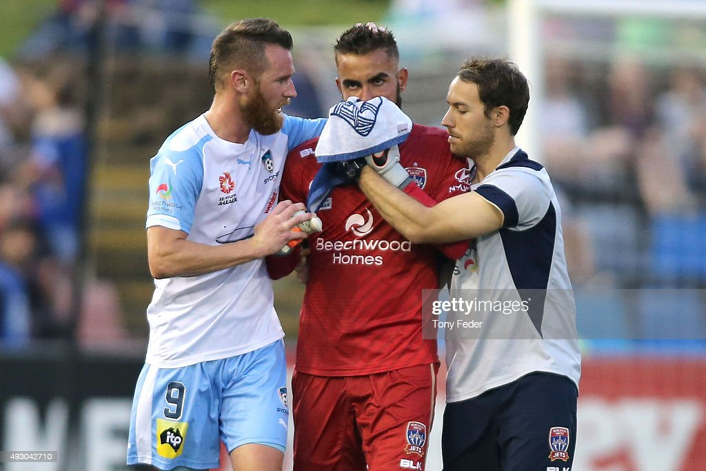 Mark Birighitti (C) of the Jets leaves the ground after getting injured he is aided by Shane Smeltz (L) of Sydney FC during the round two A-League match between the Newcastle Jets and Sydney FC at Hunter Stadium on October 17, 2015 in Newcastle, Australia.