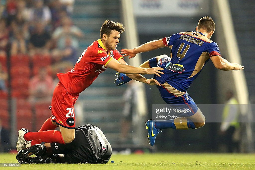 Mark Birighitti off the Jets saves a goal with Antoni Trimboli of Adelaide United and Nigel Boogaard of the Jets in frame during the round 11 A-League match between the Newcastle Jets and Adelaide United at Hunter Stadium on December 18, 2015 in Newcastle, Australia.