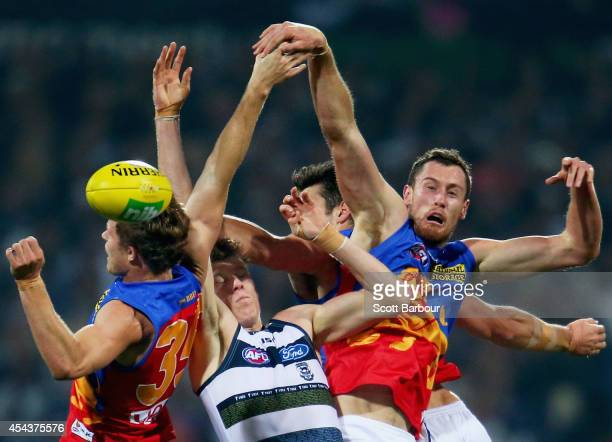 Mark Blicavs of the Cats and Matthew Leuenberger and Ryan Lester of the Lions compete for the ball during the round 23 AFL match between the Geelong...