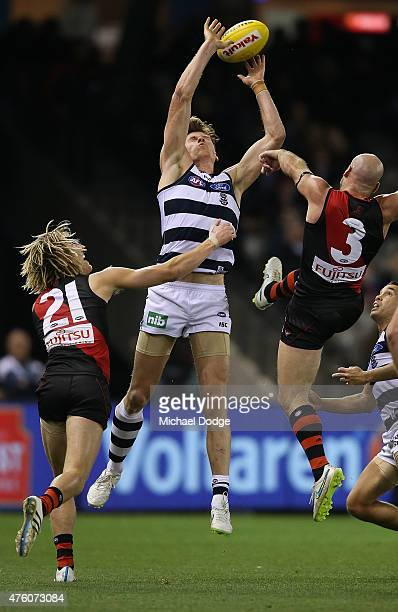 Mark Blicavs of the Cats contests the ball against Dyson Heppell and Paul Chapman of the Bombers during the round 10 AFL match between the Essendon...