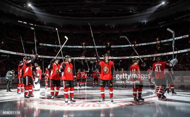 Mark Borowiecki Mike Hoffman Alex Formenton JeanGabriel Pageau and Craig Anderson of the Ottawa Senators raise their sticks to salute the crowd...