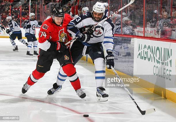 Mark Borowiecki of the Ottawa Senators battles for puck possession against Dustin Byfuglien of the Winnipeg Jets at Canadian Tire Centre on November...