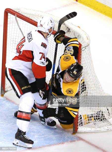 Mark Borowiecki of the Ottawa Senators checksDavid Pastrnak of the Boston Bruins into the goal during the third period at TD Garden on April 6 2017...