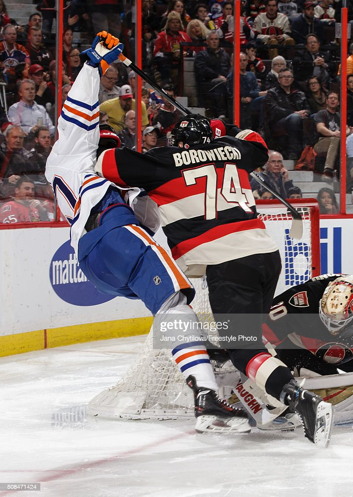 Mark Borowiecki #74of the Ottawa Senators checks Benoit Pouliot #67 of the Edmonton Oilers as he defends the net during an NHL game at Canadian Tire Centre on February 4, 2016 in Ottawa, Ontario, Canada.