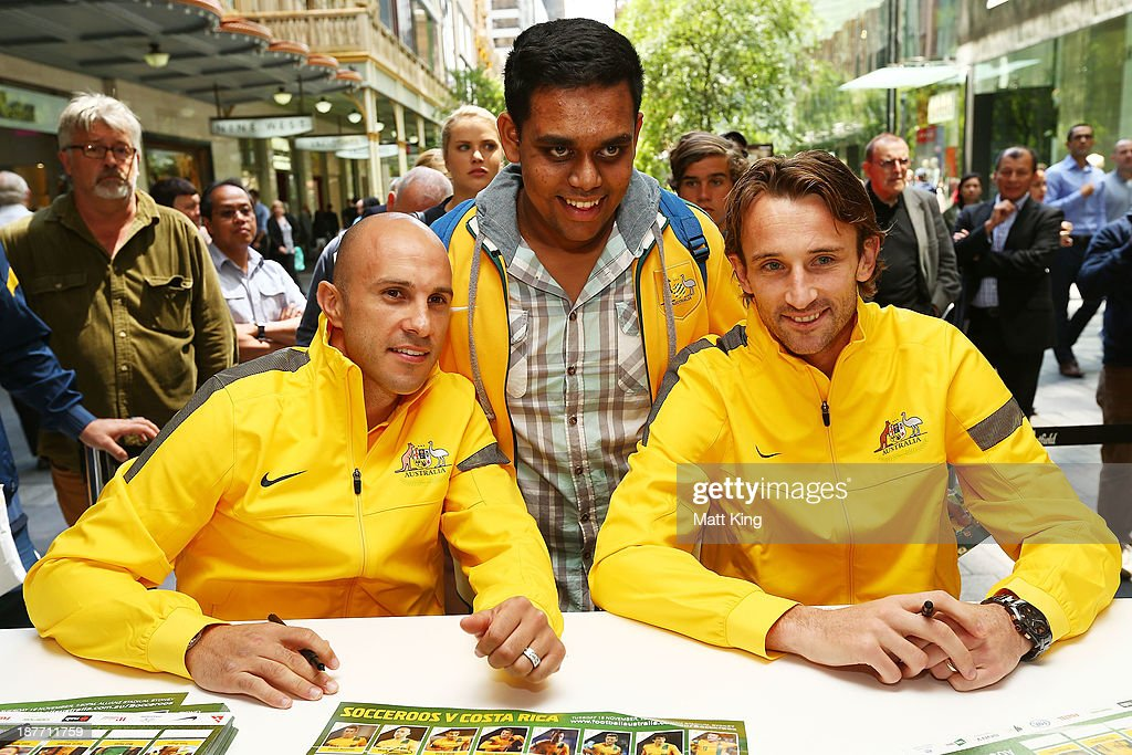 Mark Bresciano (L) and Josh Kennedy (R) pose with a member of the public during an Australian Socceroos public appearance at Westfield Sydney on November 12, 2013 in Sydney, Australia.