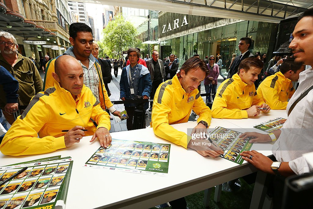 Mark Bresciano (L) and Josh Kennedy (R) sign autographs for fans during an Australian Socceroos public appearance at Westfield Sydney on November 12, 2013 in Sydney, Australia.