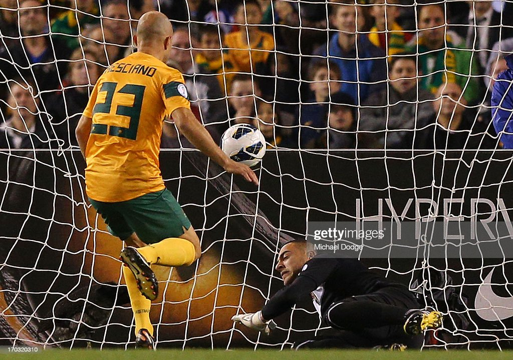 Mark Bresciano of the Socceroos kicks the ball for a goal past Jordan goal keeper Amer Shafi during the FIFA World Cup Qualifier match between the Australian Socceroos and Jordan at Etihad Stadium on June 11, 2013 in Melbourne, Australia.
