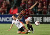 Mark Bridge of the Wanderers is challenged by Liam Miller of the Roar during the round 18 ALeague match between the Western Sydney Wanderers and...